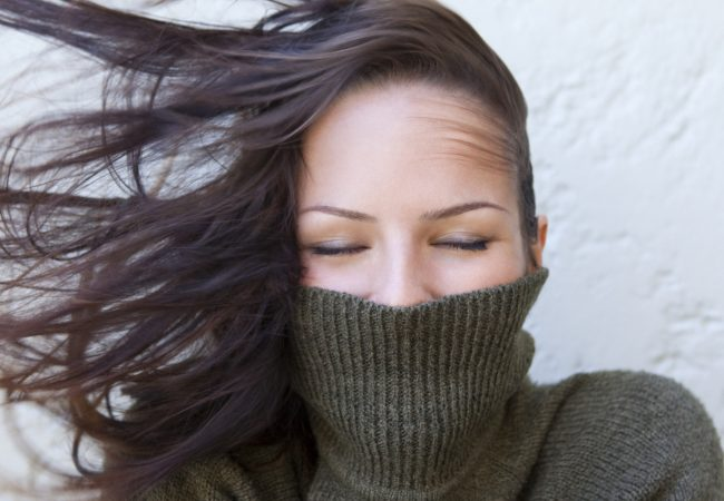 Woman with polar neck jumper and wind in her hair